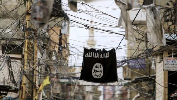 An Islamic State flag hangs amid electric wires over a street. - Sputnik Mundo