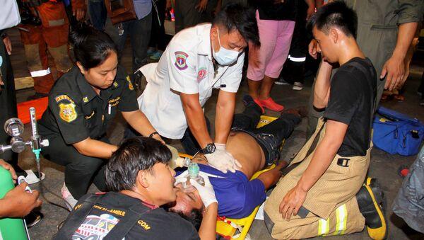 Socorristas tailandeses ayudan a un herido en un accidente en Bangkok - Sputnik Mundo
