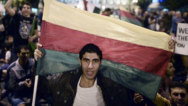 Hombre con una bandera de la PYD - Sputnik Mundo