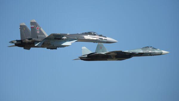 El Su-35 (izquierda) junto con el Su-57 durante un vuelo de demostración - Sputnik Mundo