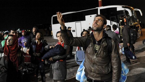 Refugees and migrants wait to board busses heading to shelters, following their arrival aboard the Blue Star Patmos passenger ship at the port of Elefsina, near Athens, Greece - Sputnik Mundo
