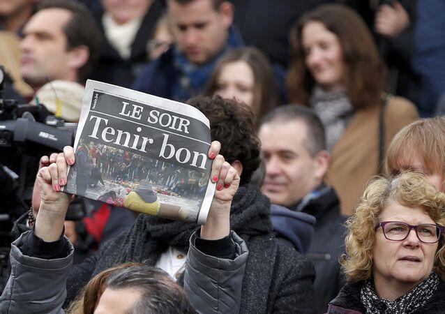 Un periódico que llama a Aguantar es usado como un cartel durante el minuto de silencio en Bruselas