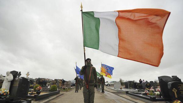 Un miembro de Sinn Fein con la bandera nacional de Irlanda - Sputnik Mundo