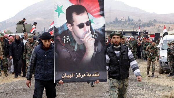 Voluntarios sirios llevan la imagen del presidente del país, Bashar Asad - Sputnik Mundo