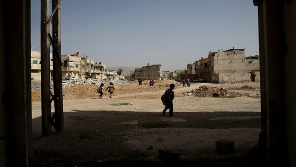 Schoolchildren carry their bags as they walk along a street in the rebel held Douma neighborhood of Damascus, Syria March 27, 2016. - Sputnik Mundo