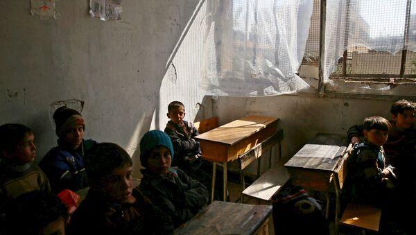 Niños sirios en una escuela destruida por bombardeos en Damasco - Sputnik Mundo