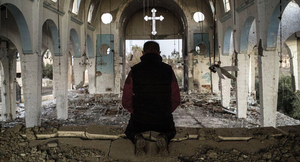 Cristiano sirio en una iglesia destruida en una aldea liberada de ISIS