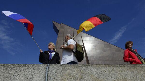Los ciudadanos sosteniendo las banderas de Rusia y Alemania en Berlín  - Sputnik Mundo