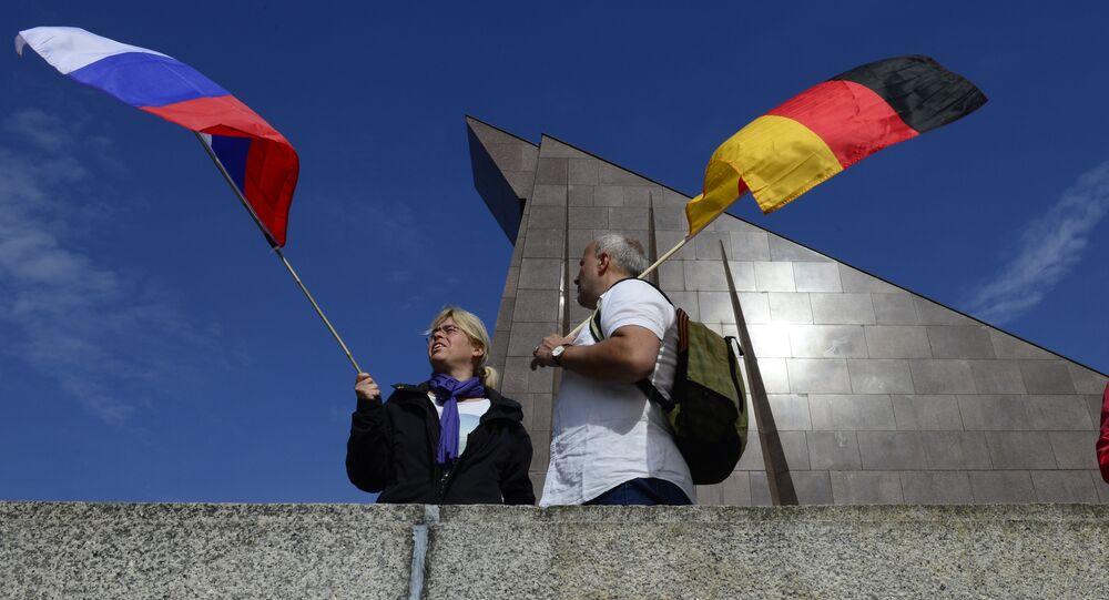 Los ciudadanos sosteniendo las banderas de Rusia y Alemania