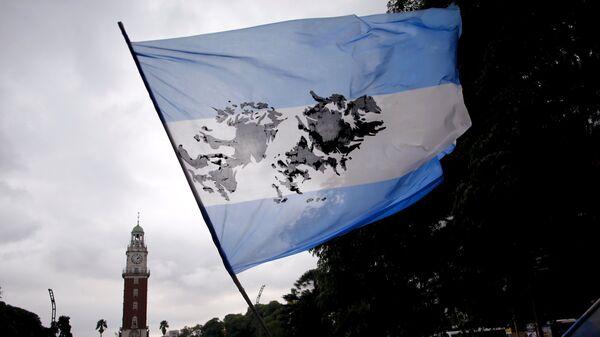 Un hombre agita una bandera argentina con una imagen de las Islas Malvinas - Sputnik Mundo
