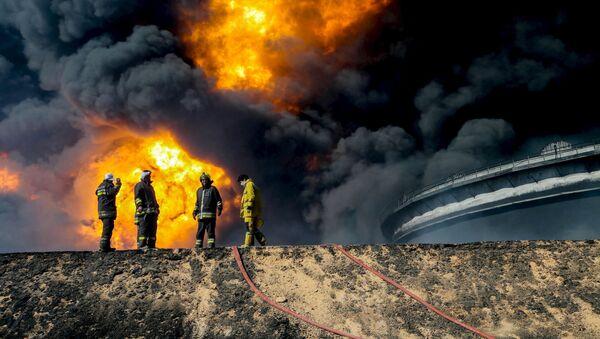Los bomberos en el lugar del incendio en los depóstios petroleros en Ras Lanuf, Libia - Sputnik Mundo