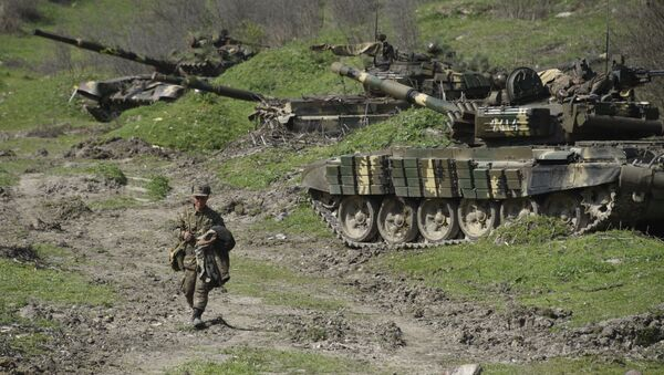A soldier of the defense army of Nagorny Karabakh walks past tanks at a field position outside the village of Mataghis, some 70km north of Karabakh's capital Stepanakert, on April 6, 2016 - Sputnik Mundo