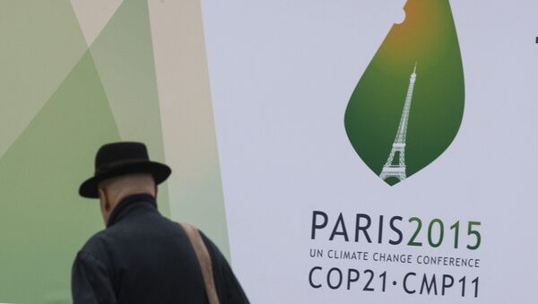 A passerby walks in front of posters for the forthcoming COP 21 World Climate Summit in Paris, France - Sputnik Mundo
