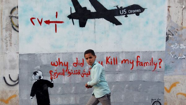 A Yemeni boy (C) walks past a mural depicting a US drone and reading  Why did you kill my family on December 13, 2013 in the capital Sanaa. - Sputnik Mundo