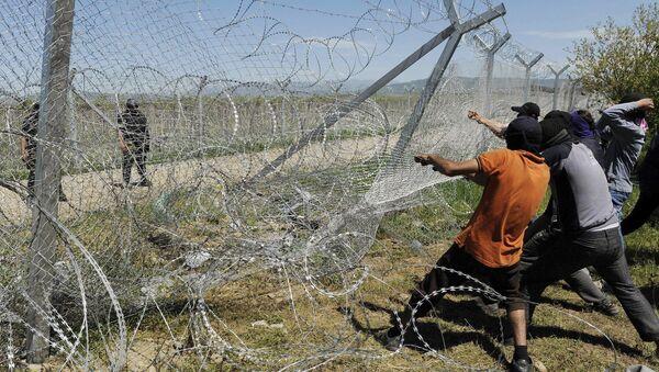 Migrantes intentan derrumbar una parte de la valla fronteriza entre Grecia y Macedonia - Sputnik Mundo
