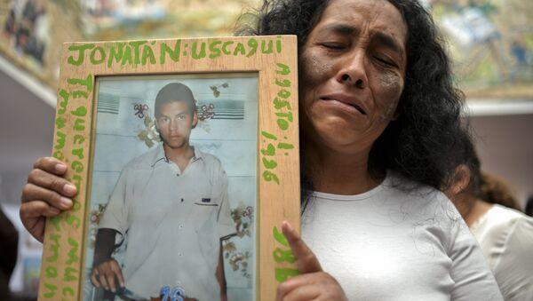 Una mujer con la foto de su hijo, desaparecido en el masacre de Trujillo por grupos paramilitares - Sputnik Mundo