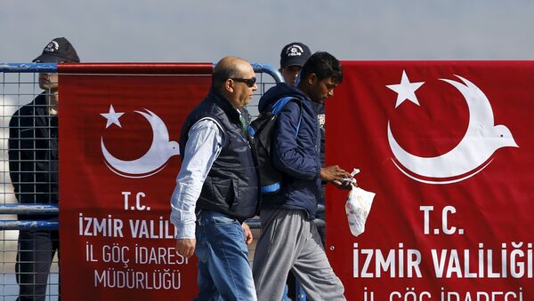 A migrant is escorted by a Turkish police officer as he arrives in the Turkish coastal town of Dikili, Turkey, April 4, 2016 - Sputnik Mundo