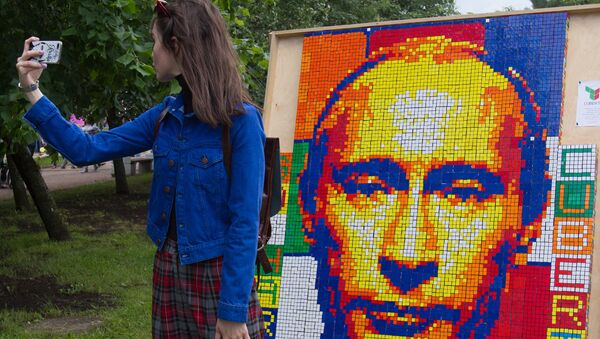 A girl takes a selfie against a portrait of Russian President Vladimir Putin composed of Rubik's Cubes at the festival of the social network VKontakte in St. Petersburg - Sputnik Mundo