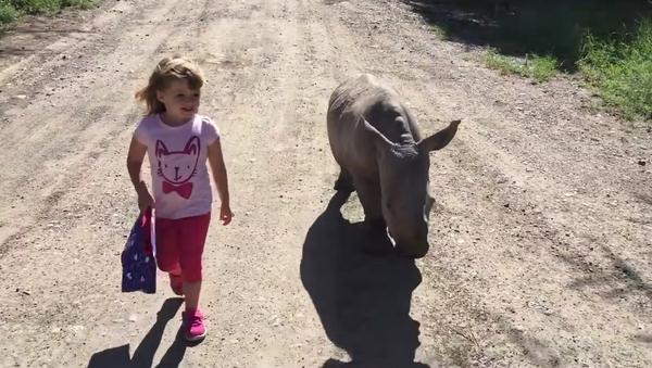 Una niña saca a pasear a una cría de rinoceronte blanco - Sputnik Mundo