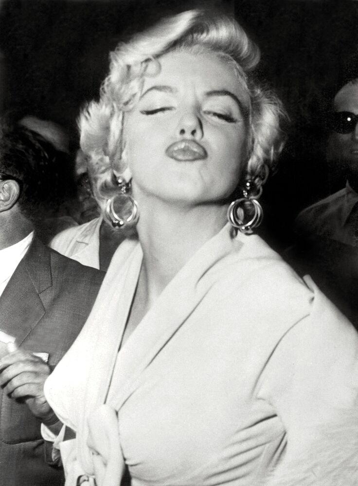 L'actrice américaine Marilyn Monroe pose devant les photographes, exécutant une grimace fort gracieuse, le 13 septembre 1954 à son arrivée à New York, où la vedette n'est pas venue depuis trois ans