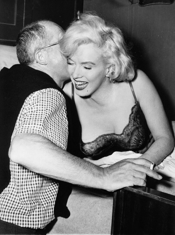 Director Billy Wilder whispers the words of advice to Marilyn Monroe, right, prior to shooting the scene from the film Some Like it Hot, in which Monroe is back to work in Hollywood for the first time in two years