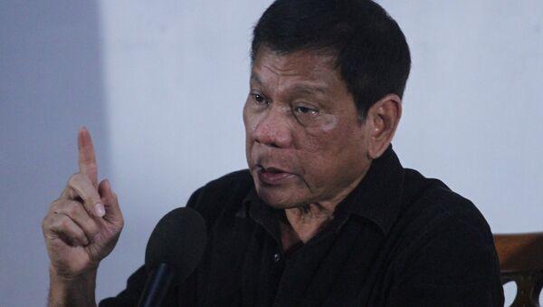 Rodrigo Duterte, presidente de Filipinas con la bandera de Filipinas - Sputnik Mundo