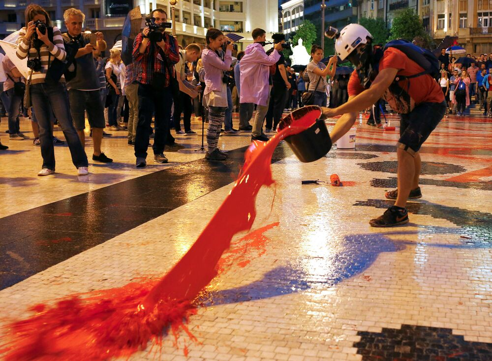 Protesters spill buckets of color paint during a protest against the government, at Central Square in Skopje, Macedonia June 6, 2016