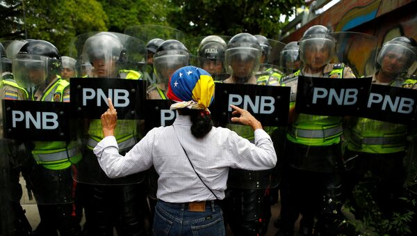 An opposition supporter argues with riot policemen during a rally to demand a referendum to remove President Nicolas Maduro in Caracas, Venezuela, June 7, 2016.  - Sputnik Mundo