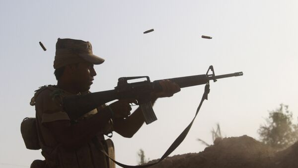 A member of the Iraqi pro-governement forces fires his weapon on a front line in the Albu Huwa area, south of Fallujah near the Euphrates river, on June 1, 2016, - Sputnik Mundo
