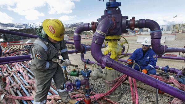 Workers tend to a well head during a hydraulic fracturing operation outside Rifle, in western Colorado - Sputnik Mundo