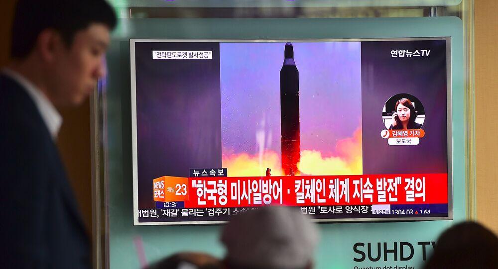 Un hombre cerca de la pantalla donde se muestra una noticia sobre una prueba realizada por Corea del Norte de misil Musudan