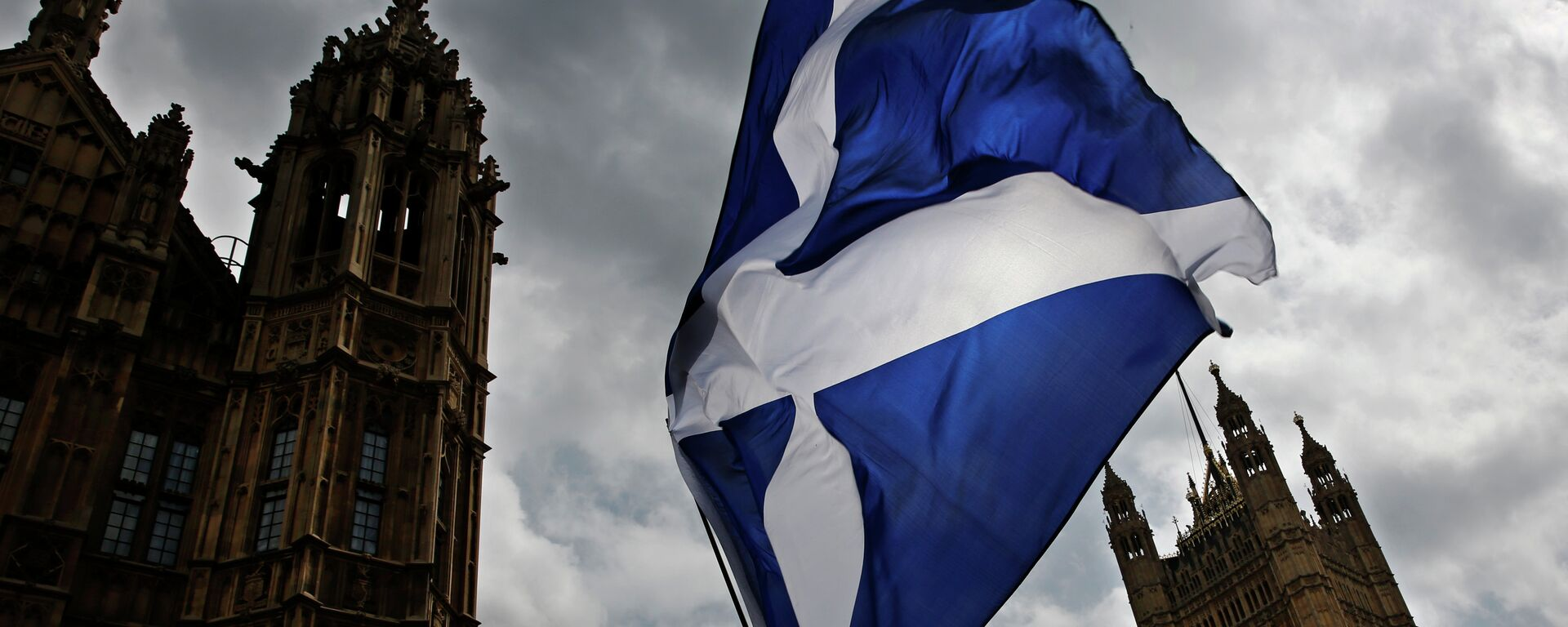 A member of public flies a giant Scottish Saltire flag outside the Houses of Parliament shortly before Scotland First Minister Nicola Sturgeon posed with newly-elected Scottish National Party (SNP) MPs during a photocall in London on May 11, 2015 - Sputnik Mundo, 1920, 30.03.2021