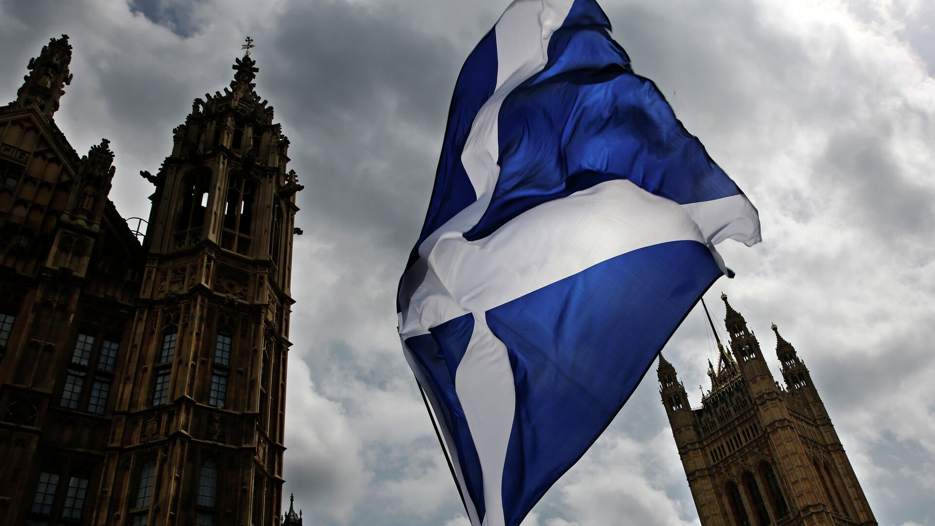 A member of public flies a giant Scottish Saltire flag outside the Houses of Parliament shortly before Scotland First Minister Nicola Sturgeon posed with newly-elected Scottish National Party (SNP) MPs during a photocall in London on May 11, 2015 - Sputnik Mundo, 1920, 22.03.2021