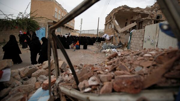 Women walk past destroyed houses during a vigil marking one year since a Saudi-led air strike on a residential area in Sanaa, Yemen June 21, 2016. - Sputnik Mundo