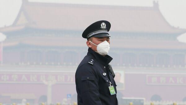 Policía chino con una máscara respiratoria - Sputnik Mundo