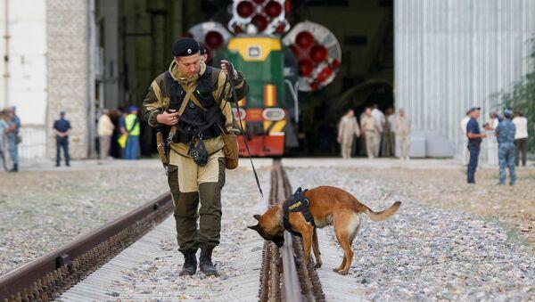 Полицейский с собакой перед ракетой-носителем Союз- ФГ с пилотируемым кораблем Союз-МС на космодроме Байконур - Sputnik Mundo