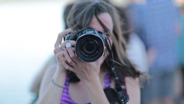 Una mujer saca una foto - Sputnik Mundo