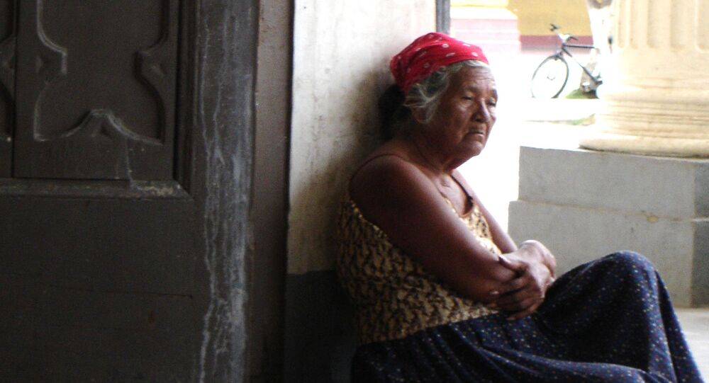Una vieja sentada en el zaguán