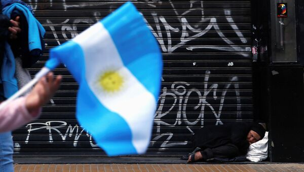 A woman sleeps on the sidewalk as a girl passes by holding an Argentine national flag during celebrations of the bicentennial anniversary of Argentina's independence from Spain in Buenos Aires - Sputnik Mundo