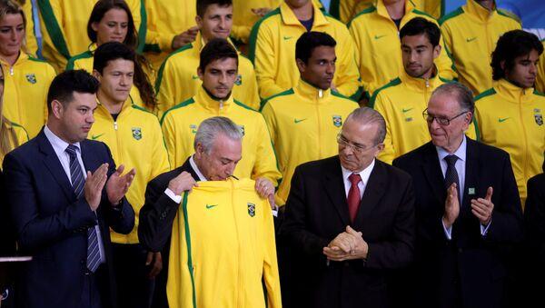 Brazil's interim President Michel Temer receives a jacket for the Brazil uniform, during a presentation ceremony of the Delegation of the Olympic Athletes at the Planalto Palace in Brasilia, Brazil July 13, 2016. - Sputnik Mundo