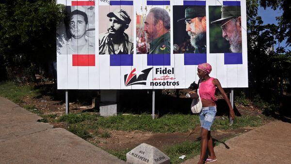 Mujer pasa junto a la pancarta Fidel con nosotros, Cuba - Sputnik Mundo
