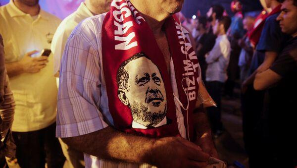 Simpatizante del presidente de Turquía,Tayyip Erdogan, con una bufanda con su imagen - Sputnik Mundo