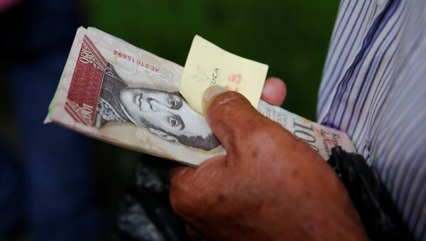 A man holds Venezuelan bolivar notes as he queues trying to buy basic food during a special inspection of Venezuelan soldiers to a municipal market in Caracas, Venezuela July 15, 2016 - Sputnik Mundo