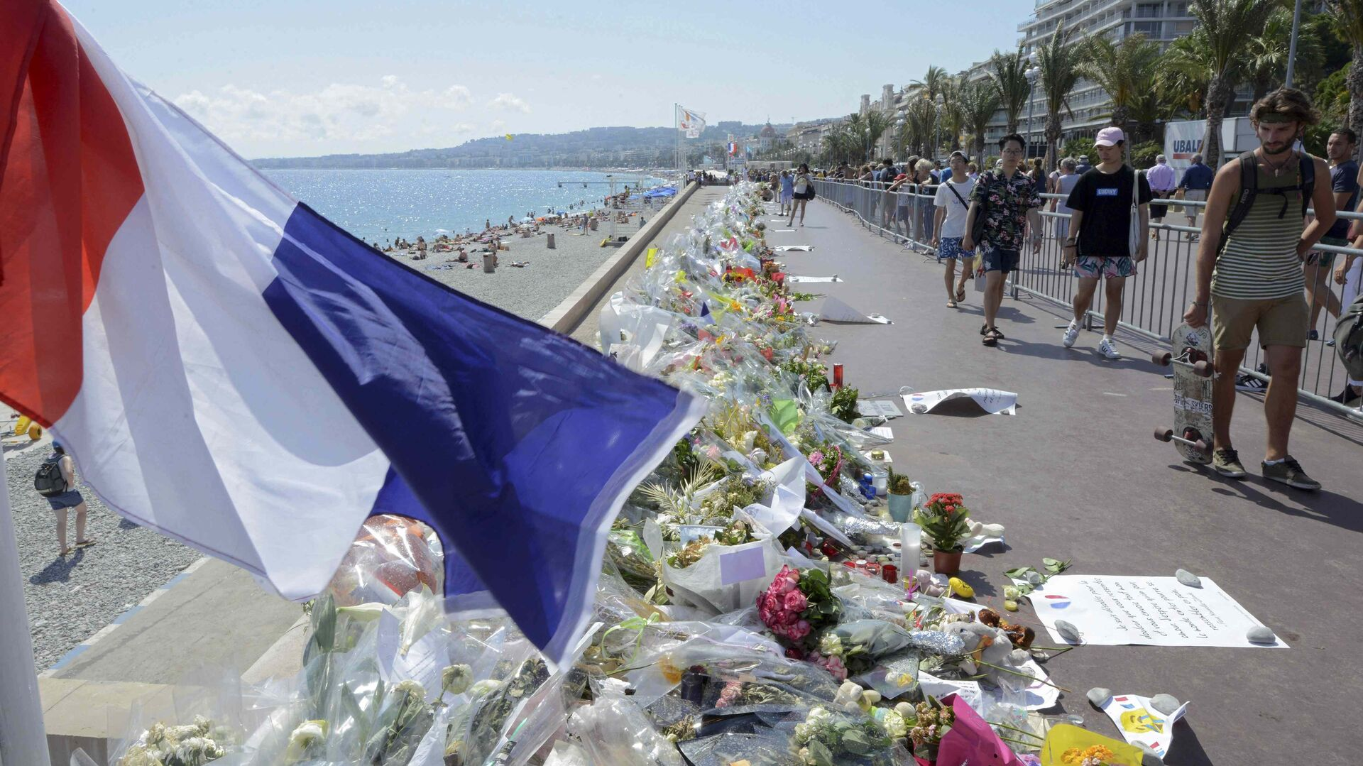 People walk past flowers left in tribute at a makeshift memorial to the victims of the Bastille Day truck attack near the Promenade des Anglais in Nice - Sputnik Mundo, 1920, 11.03.2021