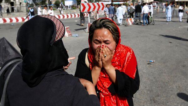 Una mujer afgana llora en el sitio de atentado en Kabul - Sputnik Mundo