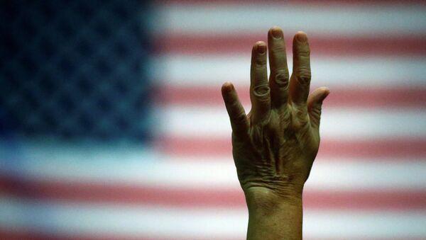 Partidario del candidato presidencial Donald Trump levanta la mano durante un evento de la campaña electoral - Sputnik Mundo