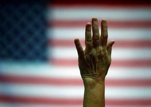 Partidario del candidato presidencial Donald Trump levanta la mano durante un evento de la campaña electoral
