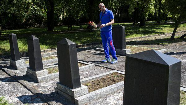 Un hombre deposita flores en una tumba - Sputnik Mundo