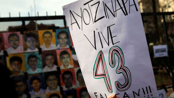 A woman holds up a sign that reads Ayotzinapa lives - 43 are missing - Sputnik Mundo