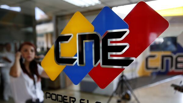 People walk past a logo of the National Electoral Council (CNE) at its headquarters in Caracas - Sputnik Mundo